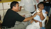Dr. Bibiano Fajardo performs Hilot diagnosis on a child.
