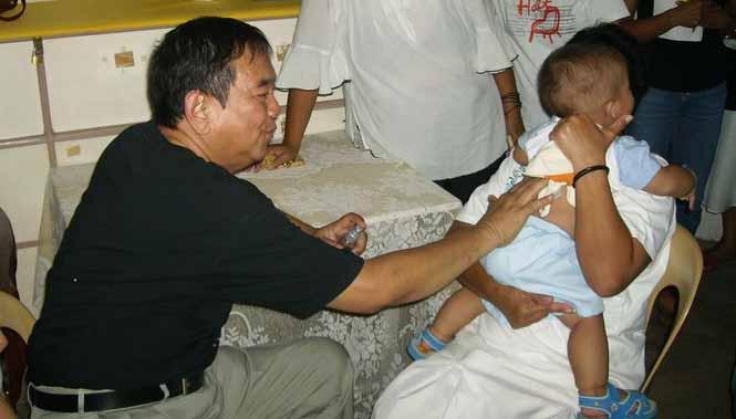 Dr. Bibiano Fajardo performs Hilot diagnosis on a child.