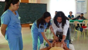 ATHAG Hilot therapists Jhen Dellosa and Mary Flor Alvarez teach a mother how to do Hilot on her daughter.