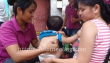 A baby gets a traditional Hilot healing session at Payatas.